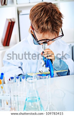 Cute boy is lookingin his microscope in a laboratory. Education.