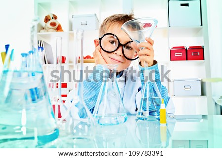 Cute boy is making science experiments in a laboratory. Education. - stock photo