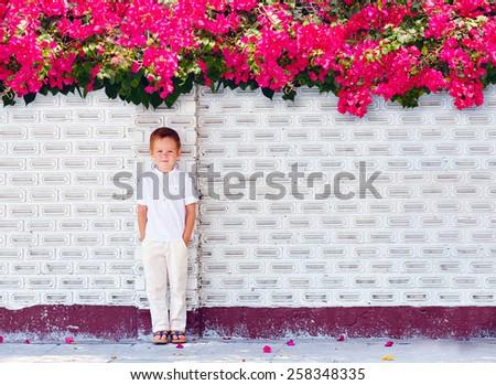cute boy kid standing near blooming wall - stock photo