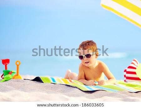 cute boy kid sunbathing on the beach - stock photo