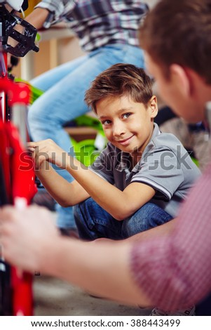 Cute boy learning to repair his bike - stock photo