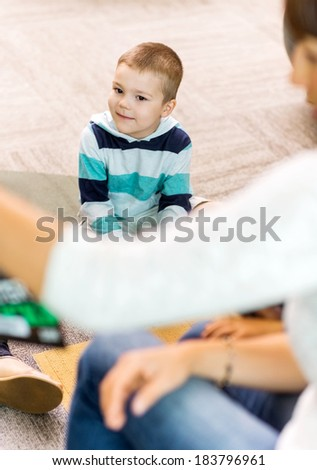Cute boy listening to teacher in library of elementary school - stock photo