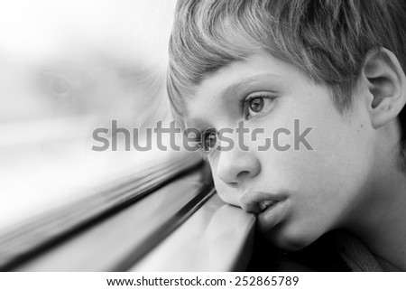Cute Boy looking through the window - stock photo