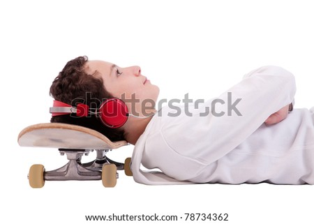 cute boy lying on his back, listening to music with his head on a skateboard, isolated on white,studio shot