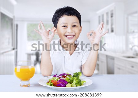 Cute boy making OK gesture while having salad, shot in the kitchen