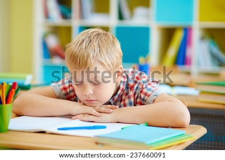 Cute boy napping by desk in classroom