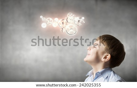 Cute boy of school age looking up at gears mechanism - stock photo