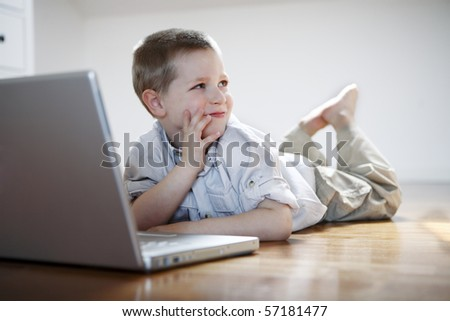 Cute boy on a laptop laying down on the floor - stock photo