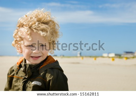 cute boy on the beach looking at the camera - stock photo