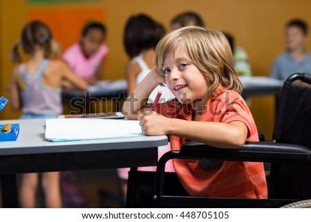 Cute boy on wheelchair writing on book in classroom