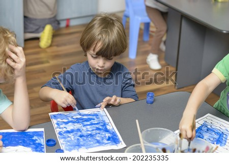 Cute boy painting at kindergarten - stock photo