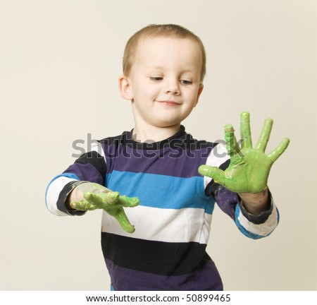 Cute boy painting with finger colors isolated - stock photo