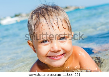 Cute boy playing and swimming in the transparent sea - stock photo