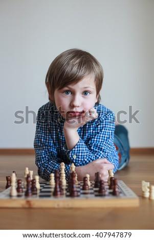 cute boy playing chess   - stock photo