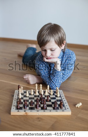 cute boy playing chess (soft focus)  - stock photo