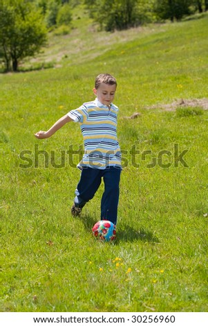 Cute boy playing football outdoor - stock photo
