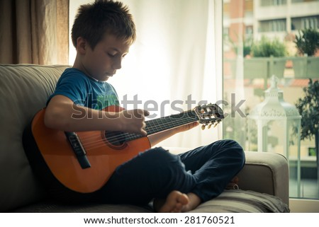 Cute boy playing guitar - stock photo