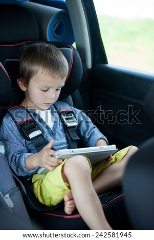 Cute boy, playing on tablet in the car, while traveling - stock photo