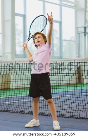 Cute boy playing tennis and posing in court indoor - stock photo