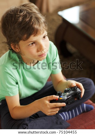 Cute boy playing video games at home - stock photo