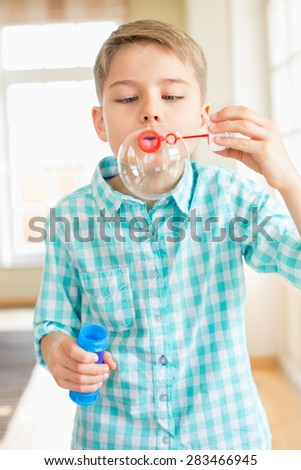 Cute boy playing with bubble wand at home - stock photo