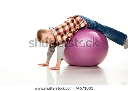 Cute boy playing with fit ball isolated on white - stock photo