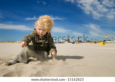 cute boy playing with sand on the beach - stock photo