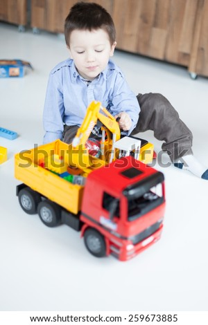 Cute boy playing with toy trucks at home - stock photo