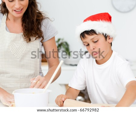 Cute boy preparing christmas biscuits with his mother in the kitchen - stock photo