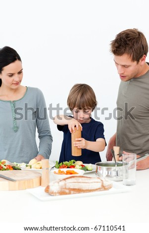 Cute boy putting salt and pepper in his salad in the kitchen with his parents - stock photo