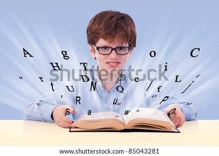 cute boy reading a book on his desk, with flying letters, isolated on blue, studio shot