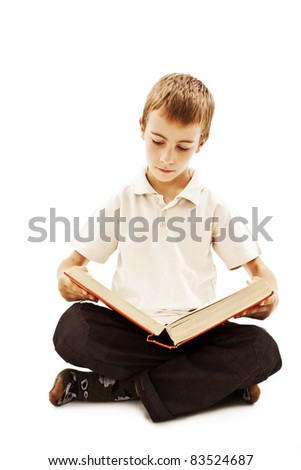 Cute boy reading a book on the floor, isolated on white, studio shot - stock photo