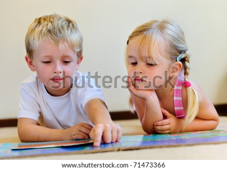 cute boy reads to adorable little blonde girl in school - stock photo