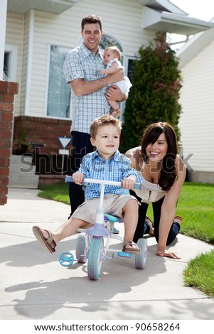 Cute boy riding cycle while happy mother watching him ride - stock photo