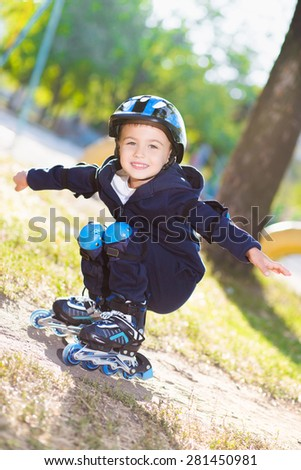Cute boy rollerblading near the playground with spaced apart arms - stock photo