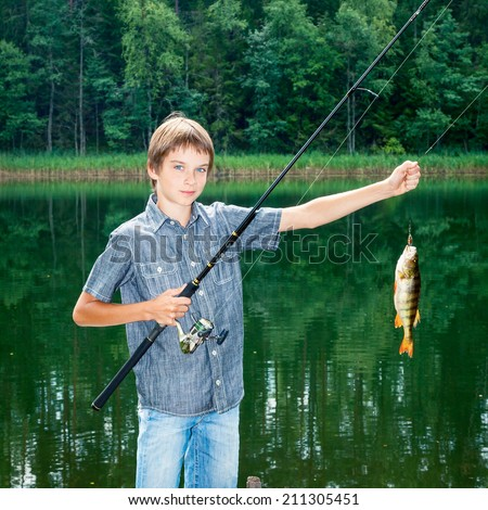 Cute boy showing fish he caught while fishing - stock photo