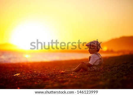 cute boy sitting by the sea at sunset alone - stock photo