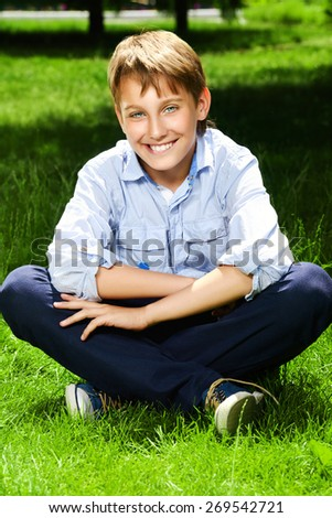 Cute boy sitting on a grass at a park and smiles. Summer day. Holiday. - stock photo