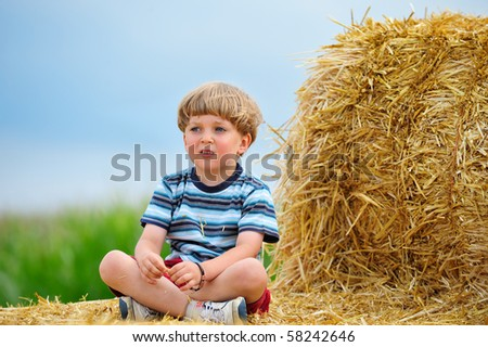 cute boy sitting on a large hay bale in the field - stock photo