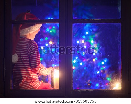 Cute boy, sitting on a window shield, playing on mobile phone at night, christmas time, waiting for Santa Claus, blue filter applied - stock photo