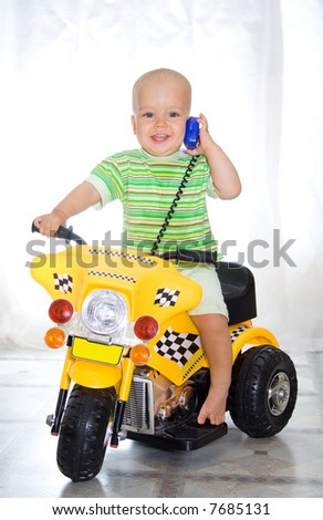 Cute boy sitting on motorcycle. At window background - stock photo