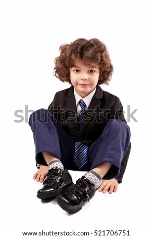 Cute boy sitting on the floor by bending the legs and looking at the camera. White background.