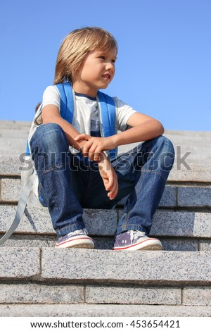 Cute boy sitting on the steps with his backpack. Back to school concept. - stock photo