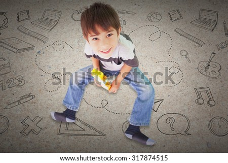 Cute boy sitting with building blocks against path - stock photo