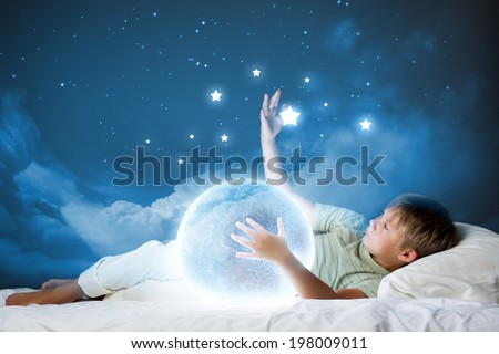 Cute boy sleeping in bed with moon - stock photo