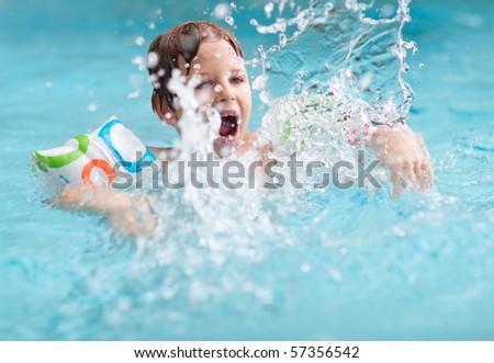 Cute boy splashing in swimming pool - stock photo