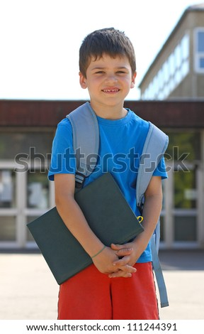 Cute boy standing in front of the school with a book