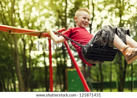 Cute boy swinging in a park - stock photo