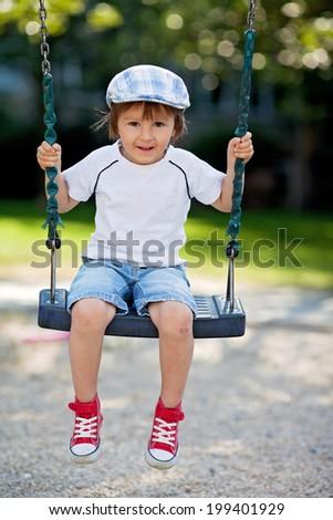 Cute boy, swinging on the playground - stock photo