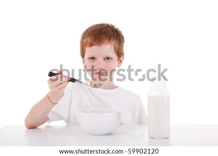 cute boy taking breakfast, isolated on white, studio shot - stock photo